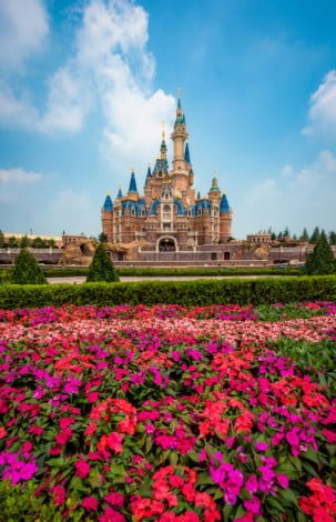enchanted-storybook-castle-daytime-puffy-clouds-flowers-shanghai-disneyland
